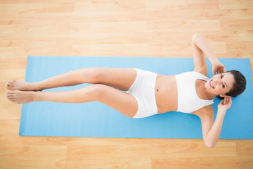 Fit woman doing abdominal crunches and smiling at camera