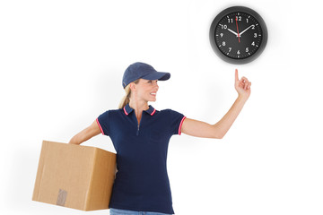 Happy delivery woman holding cardboard box and pointing up against black clock