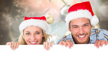Young festive couple against blurred christmas background