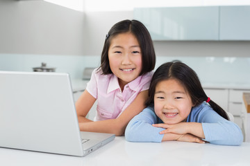Two smiling young girls with laptop in kitchen