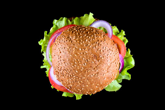 Burger isolated on black background. Fresh tasty and appetizing cheeseburger. Vegetarian burger top view