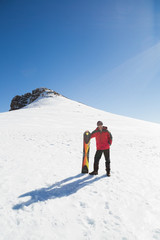 Man with ski board on snow covered landscape