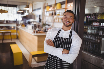 Portrait of smiling young handsome waiter with arms crossed leaning on cabinet