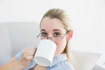 Attractive calm businesswoman sitting on couch drinking from cup