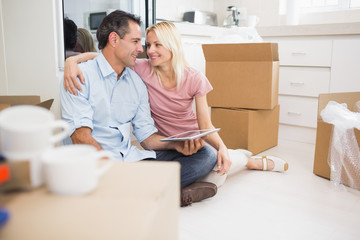 Couple using digital tablet amid boxes in a new house