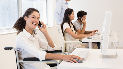 Casual businesswoman in wheelchair on the phone smiling at camera