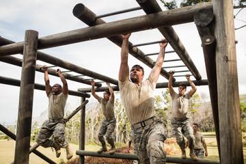 Soldiers climbing monkey bars