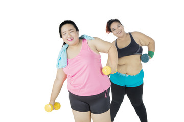 Two fat women exercising with dumbbells