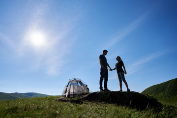 Silhouette of a romantic couple holding hands standing on a stone near a tent against a blue sky with a bright sun on a summer day. Copy spase