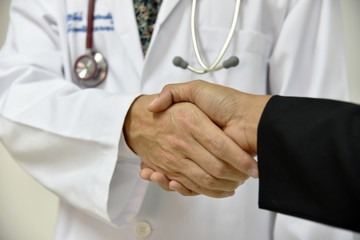 Male Doctor shaking a patient's hands;