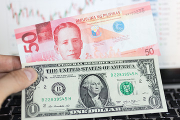Hand hold one dollar and 50 Philippines peso banknotes, notebook screen with graph at background