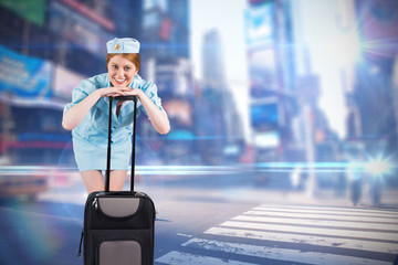 Pretty air hostess smiling at camera against blurred new york street