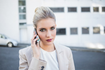 Serious stylish businesswoman having a phone call