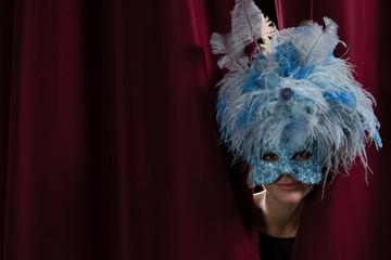 Female artist in masquerade mask peeking through the red curtain