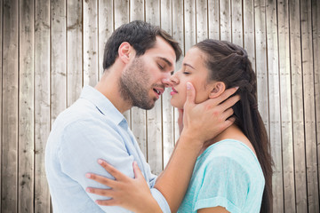 Attractive young couple about to kiss against wooden planks background