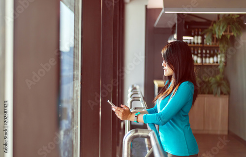 asian woman passenger holding smartphone and checking flight or