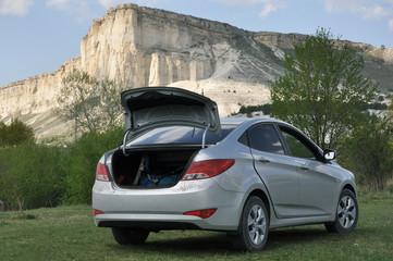 Машина с открытым багажником у подножия Белой скалы
