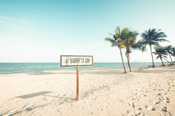Wall Mural - Landscape of coconut palm tree on tropical beach in summer. beach sign for surfing area. Vintage effect color filter.