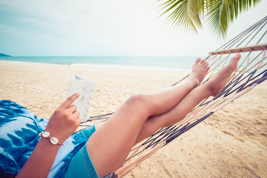 Leisure in summer - Beautiful tanned of sexy women. sunbathe relax and reading a book on hammock at sandy tropical beach. vintage color styles