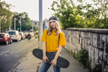 Pretty girl holding a skateboard