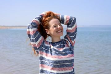 Hübsche rothaarige Frau lacht mit geschlossenen Augen an einem Strand Meer im Hintergrund