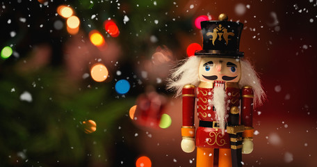 Tuinposter Historisch mon. Snow falling against close-up of nutcracker toy solider christmas decoration