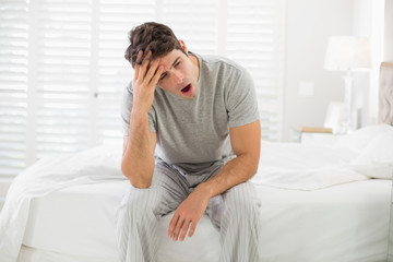 Sleepy young man sitting and yawning in bed