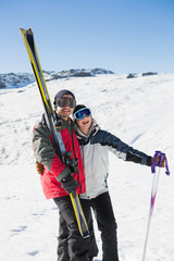 Cheerful couple with ski boards on snow