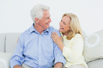 Cheerful loving senior couple sitting on sofa