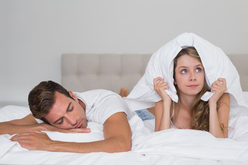 Angry woman holding pillow besides sleeping man in bed