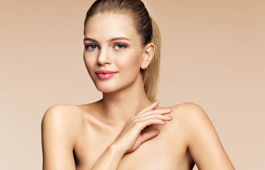 Young woman with beautiful make up looks at the camera. Photo of attractive woman with perfect skin on beige background. Skin care concept