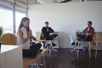 Business people doing yoga at office