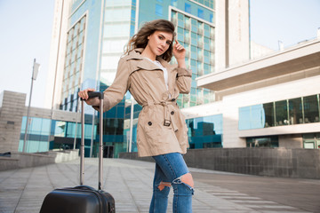 The journey of a thousand miles begins with a single step! Trendy good-looking beautiful lady standing with her luggage near the airport, going to fly away.
