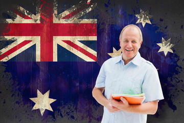 Mature student holding notebooks against australia flag in grunge effect