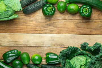 Frame from Fresh Raw Organic Green Vegetables Savoy Cabbage Zucchini Cucumbers Bell Peppers Avocados on Weathered Plank Barn Wood. Superfoods Vegan Plant Based Diet Concept. Banner Copy Space