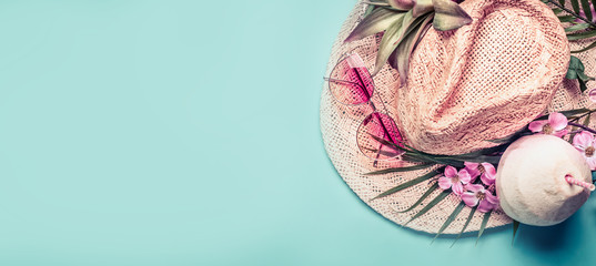 Summer holiday banner.  Beach accessories : straw hat, palm leaves, pink sun glasses, flowers and coconut cocktail on blue turquoise background, top view. Tropical vacation travel concept