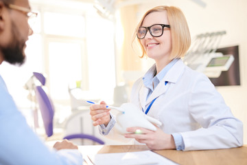 Friendly blond-haired dentist wearing white coat and eyeglasses sitting opposite her male patient and explaining him stages of treatment with help of tooth model