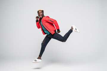 Full length portrait of a happy smiling african man running isolated over gray background