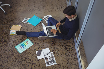 Businessman sitting on floor while working in creative office