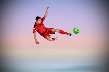 Fit football player jumping and kicking against purple background