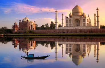 Wall Mural - Taj Mahal Agra at sunset with wooden boat on river Yamuna.