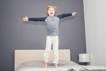 Playful boy with arms outstretched having fun in bedroom.