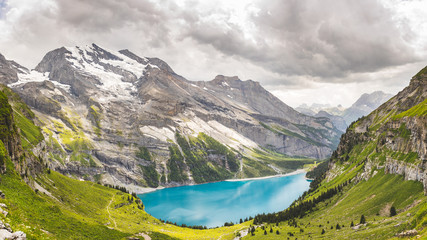 Oeschinen Lake in Swiss alps, clouds in the sky