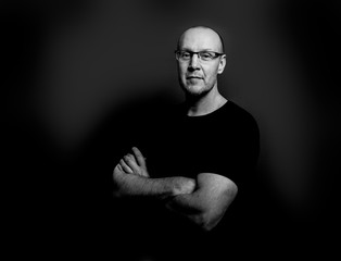 Black and white studio portrait of a middle aged man wearing glasses and smiling with arms crossed in a black t-shirt against a black background