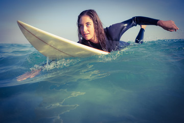 woman in wetsuit surfing