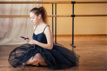 young and beautiful woman in ballet dress and pointe looking to the phone and listening to music. The ballerina does selfie on the phone in the classroom. The ballerina's girl in a dress and phone.