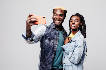 Portrait of a happy young african couple grimacing while standing together and taking a selfie isolated over gray background