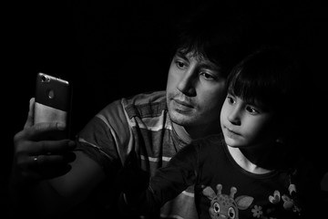 Portrait of a father and daughter in a low key. do selfie