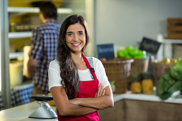 Smiling woman vendor standing at the counter in grocery store with arms crossed