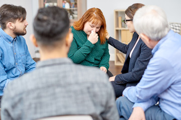 Crying fair-haired woman suffering from eating disorder discussing faced problem with other patients while participating in group therapy session, pretty psychiatrist comforting her